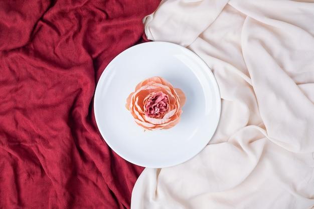 Unico fiore sul piatto bianco con tovaglie rosse e rosa.
