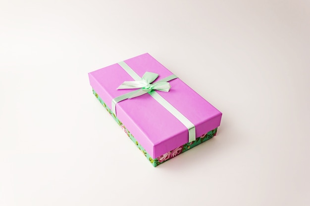 Single flowered gift purple lid paper cardboard box with green cover and bow on white . holiday present concept. close up view. selective soft focus. text copy space.