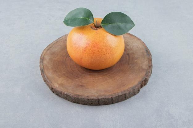 Clementina fresca singola su pezzo di legno