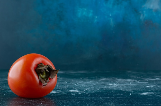 Single fresh persimmon on marble table.