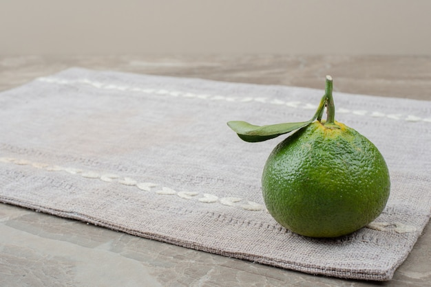 Single fresh tangerine on gray tablecloth.