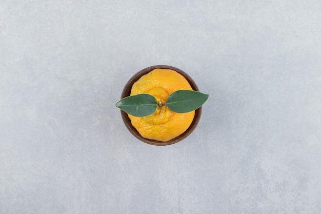 Mandarino fresco singolo con foglie in ciotola di legno.