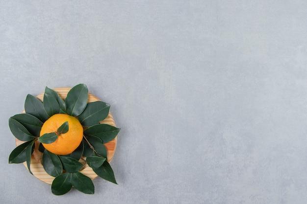 Mandarino fresco singolo con foglie sul piatto di legno.