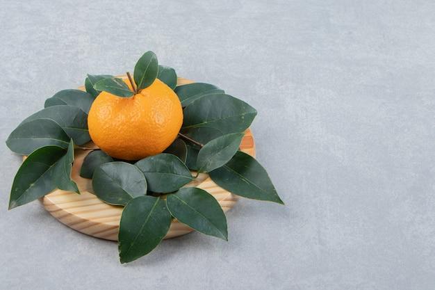 Mandarino fresco singolo con foglie su piatto di legno