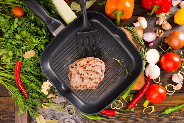 Single fried pork chop and black spatula in middle of pan surrounded by colorful fresh vegetables and herbs over wooden table