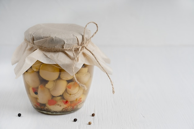 白い木製のテーブルにピクルスまたは発酵したシャンピニオンマッシュルームでいっぱいの単一のガラス瓶