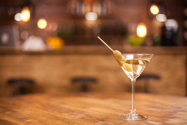 나무 테이블 위에 있는 restaurat에서 마른 마티니 한 잔. 고급스러운 빈티지 인테리어