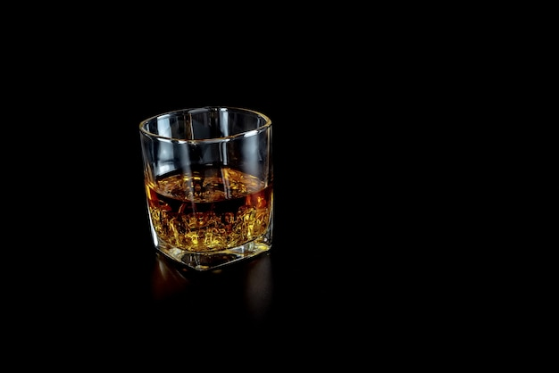 Single glass of whisky or whiskey with ice on black background.