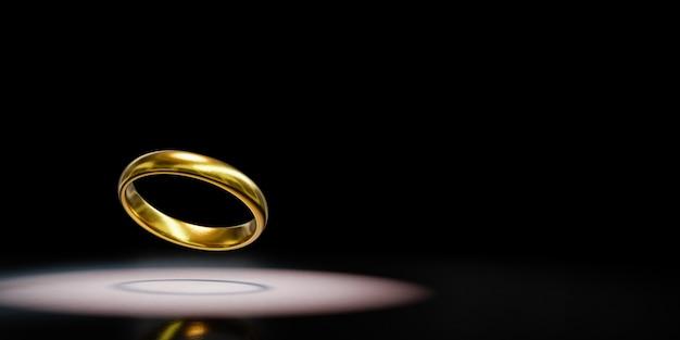 Single golden ring spotlighted on black background