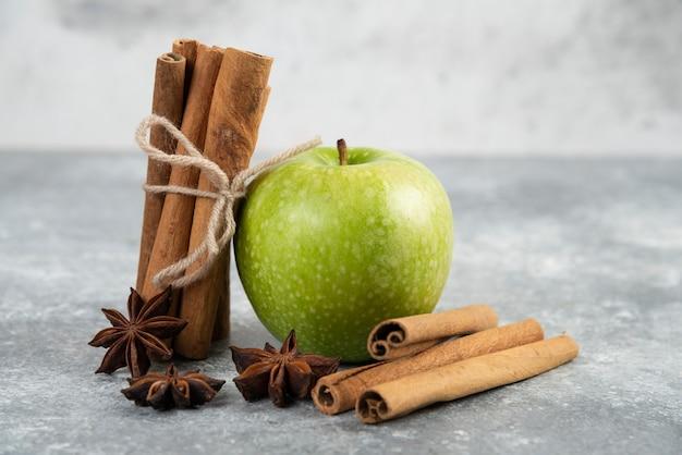 Single green apple and cinnamon sticks on marble table.