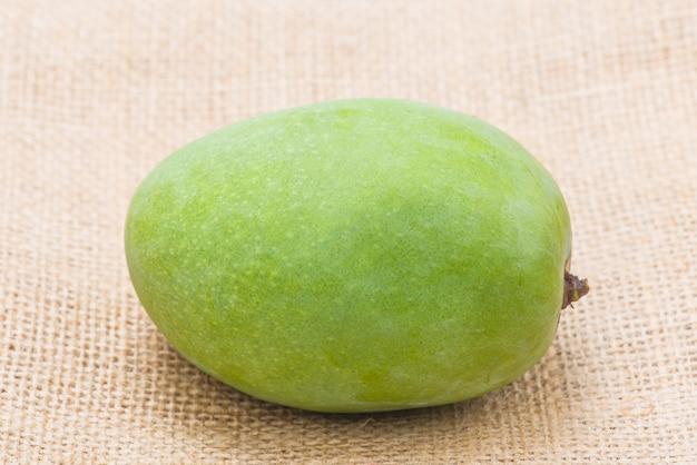 A single green mango on jute
