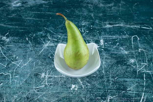 Одиночная зеленая груша в белой миске.