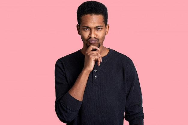 Single handsome fit black man, keeps hand on chin. guy has thoughtful fecial expressions, has interesting idea and thinks how to bring it to life. handsome male isolated on pink.