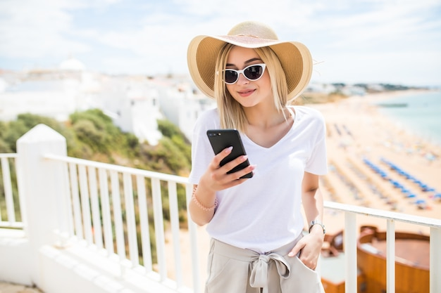 Singola ragazza felice che controlla uno smart phone seduto in una terrazza del bar