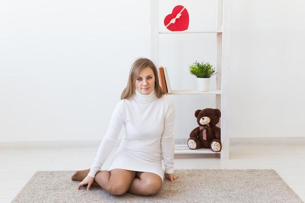 Одинокая счастливая молодая женщина сидит на полу в пустой комнате, думая о чем-то.