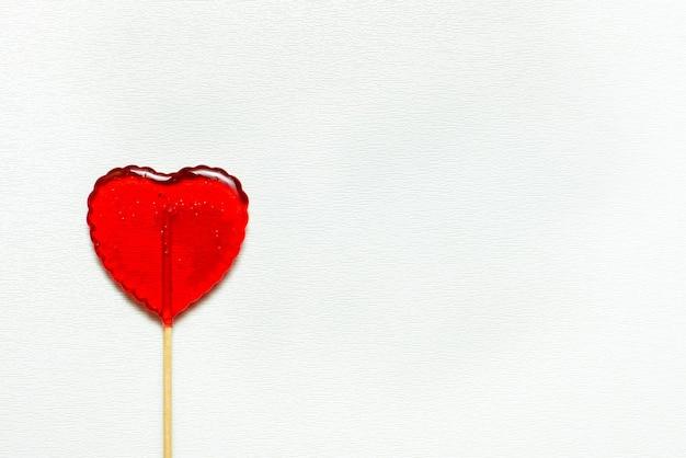 白い背景で隔離のバレンタインデーの単一のハート型のロリポップ