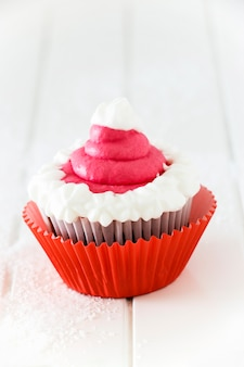 Single homemade chocolate cupcake with frosting white pink cream cheese. isolated. white wooden background.