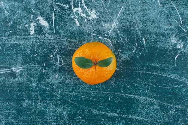 A single juicy tangerine , on the marble table.