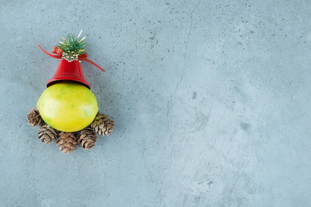 Single lemon with christmas decorations on marble.