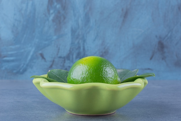 Un singolo limone con foglie in una ciotola sul tavolo di marmo.