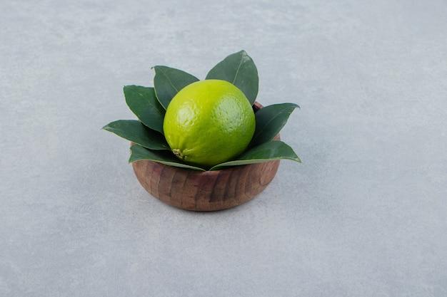 木製のボウルに葉が付いている単一の石灰。