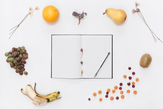 Single line notebook with notebook; pen; croissant; fruits; coffee and dried flowers on white backdrop