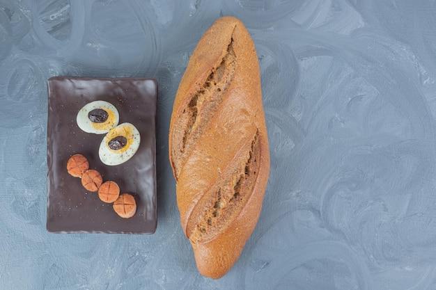Отдельная загрузка хлеба рядом с тарелкой колбасы и ломтиками яиц на мраморном столе.