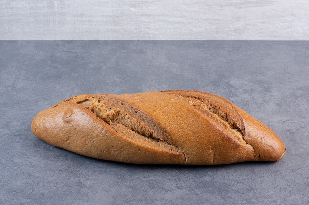 Single loaf of baton bread on marble.