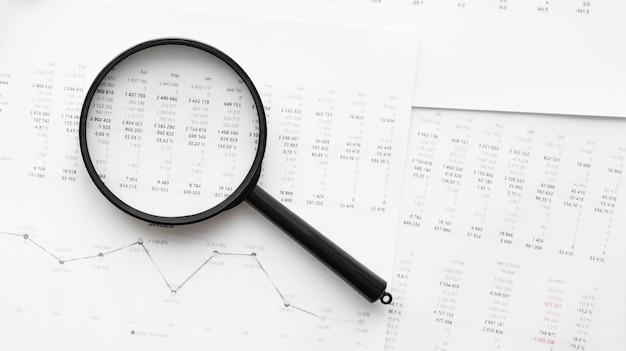 재무 데이터에 기대어 검은 손잡이가있는 단일 돋보기. 비즈니스 및 금융 연구의 개념.