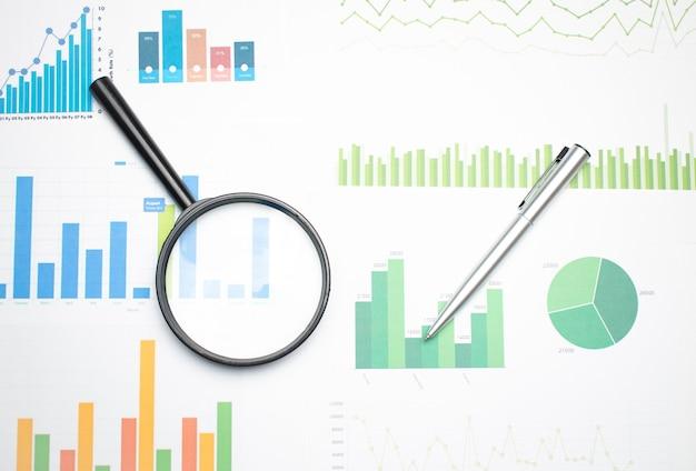 검정색 손잡이가 있는 단일 돋보기, 재무 데이터에 기대어. 비즈니스 및 금융 연구의 개념입니다.