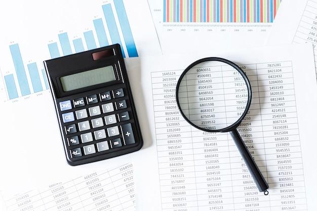 계산기가있는 단일 돋보기, 재무 데이터에 기대어. 비즈니스 및 금융 개념,