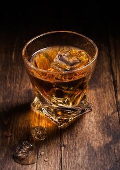 木製のテーブル表面にアイスキューブとモダンなクリスタルガラスのシングルモルトスコッチウイスキー。上面図