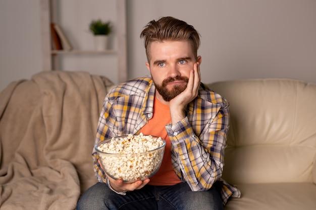 部屋でテレビを見ながらソファで独身男性