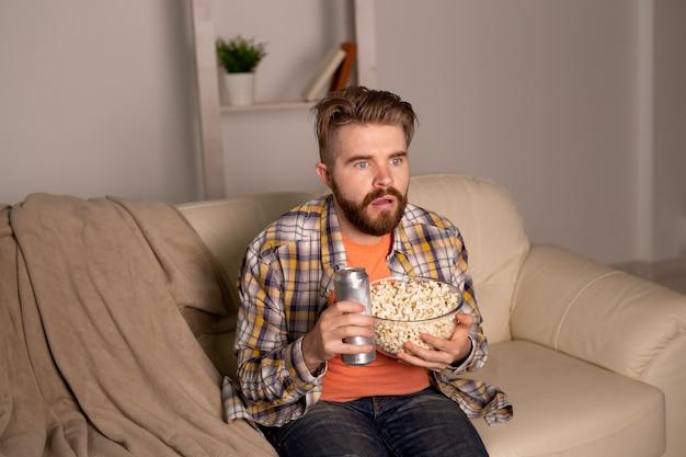 テレビを見ているソファの上の独身男性