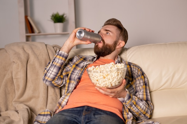 Одинокий мужчина на диване смотрит телевизор