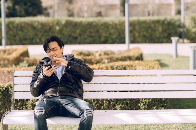 Single uomo seduto sulla panchina nel parco e parlando al telefono. foto di alta qualità