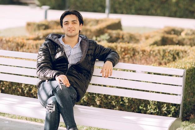 Singolo uomo seduto sulla panchina nel parco e pensare. foto di alta qualità