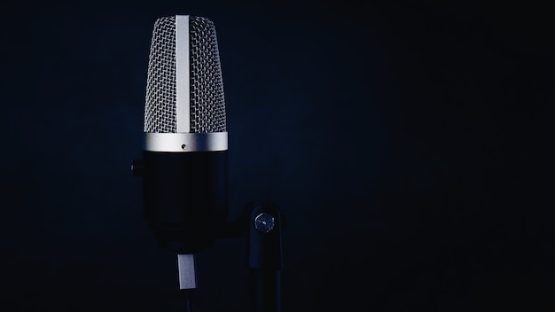 Single microphone on dark blue wall background