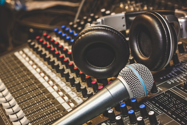 Single microphone with headphones on sound mixer board in home recording studio.