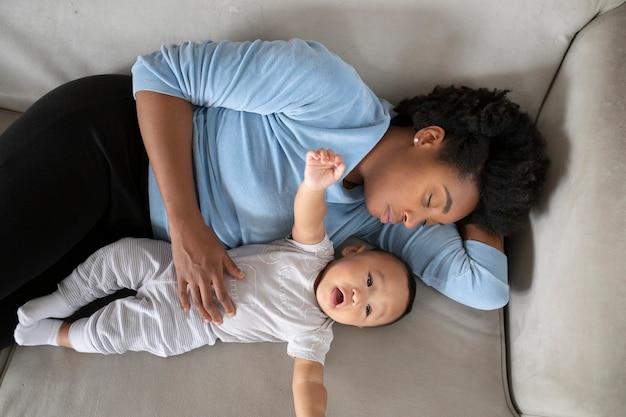 Covid19の封鎖中に彼女の赤ん坊の息子と一緒にソファに横たわっているシングルマザー