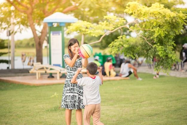 シングルママ母と息子が一緒に公園でサッカーをする