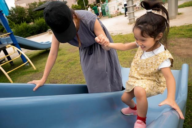 公園で娘と遊ぶシングルマザー