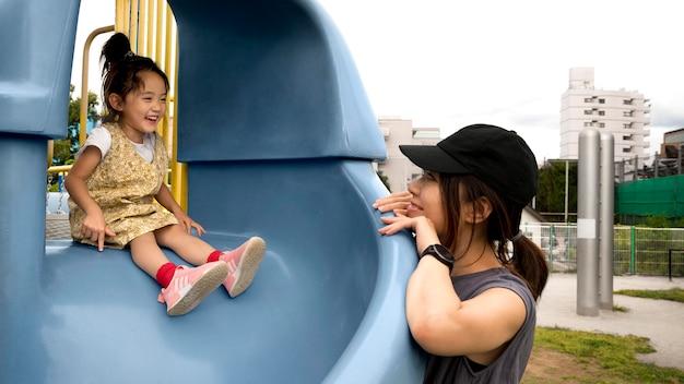 Мама-одиночка играет со своей дочерью в парке