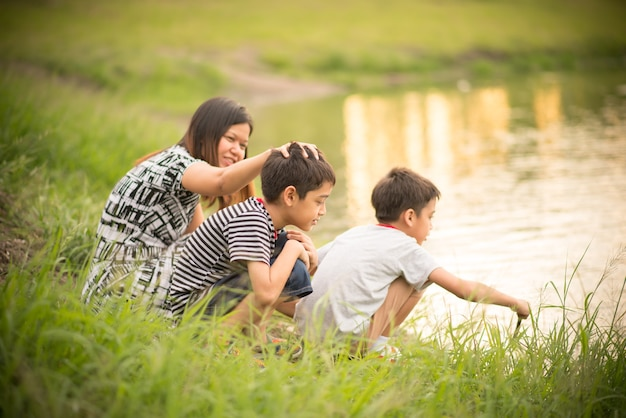 Single mom  sitting together mother and sons near the riverbank