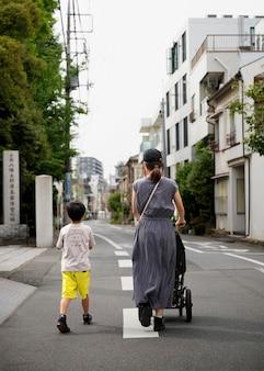 Одинокая мама гуляет со своими детьми