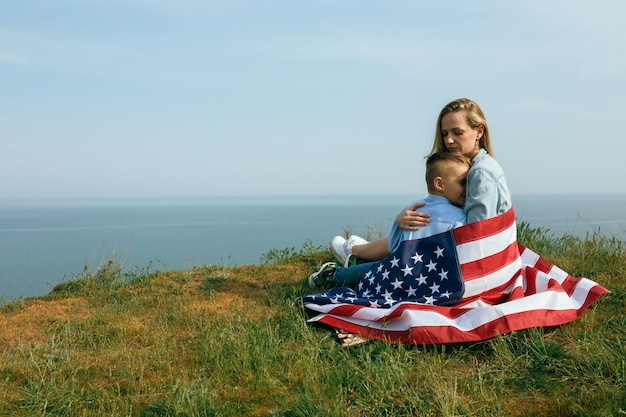 Single mother with son on independence day of usa. woman and her child walk with the usa flag on the ocean coast