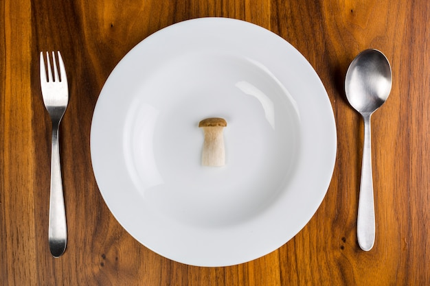 Single mushroom on a white saucer on a wooden table