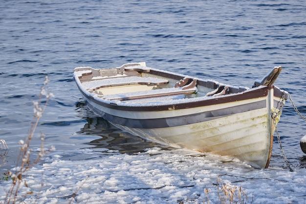 部分的に凍った湖の単一の古いボート。ボートは雪で覆われています