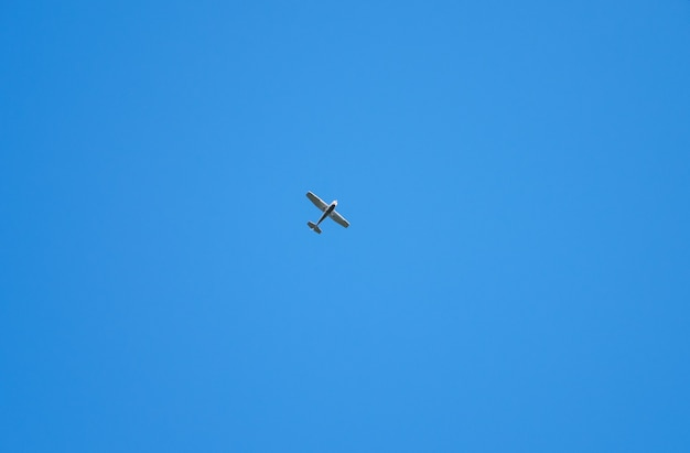 Single old retro glider high against the blue sky. airplane flies in clear sky. aircraft aviation.
