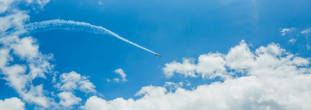 Single one sport plane of aerobatic team vapour trails in blue sky.